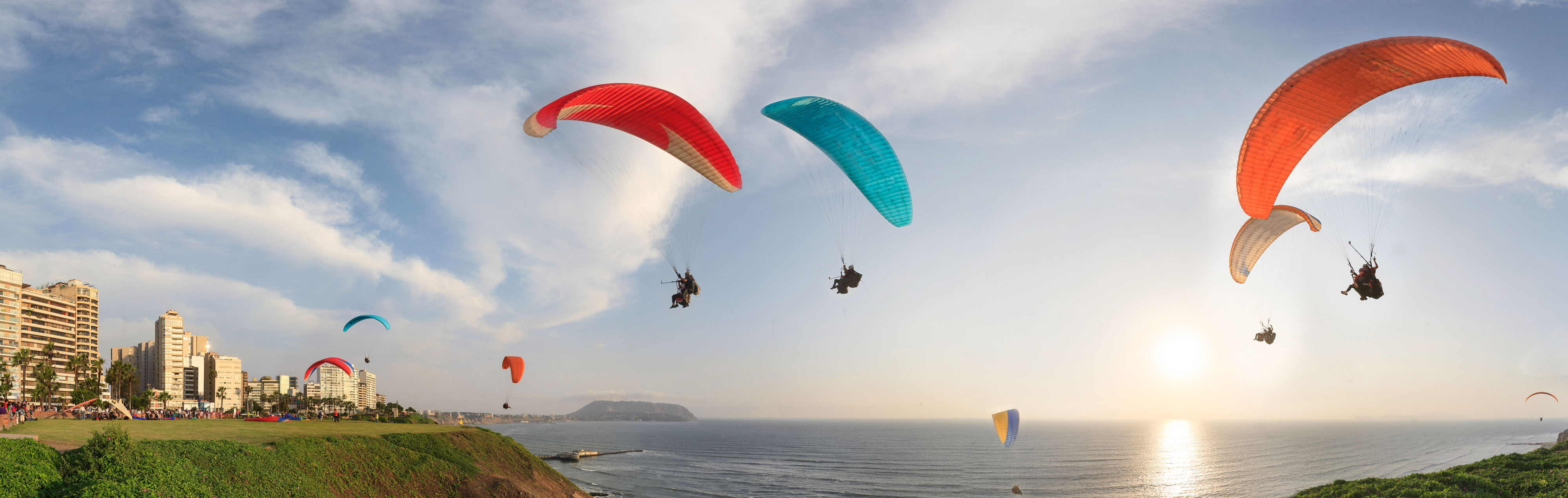 Hang gliders in Lima soar along the coast of Miraflores.