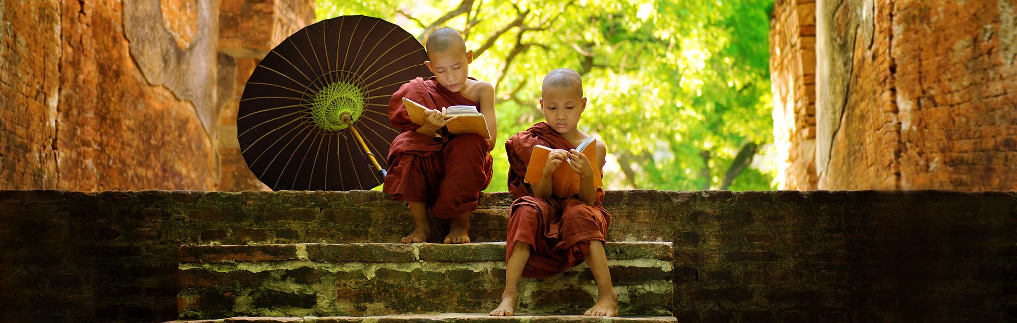 Luxury Tours - Young Buddhist monks reading on landing