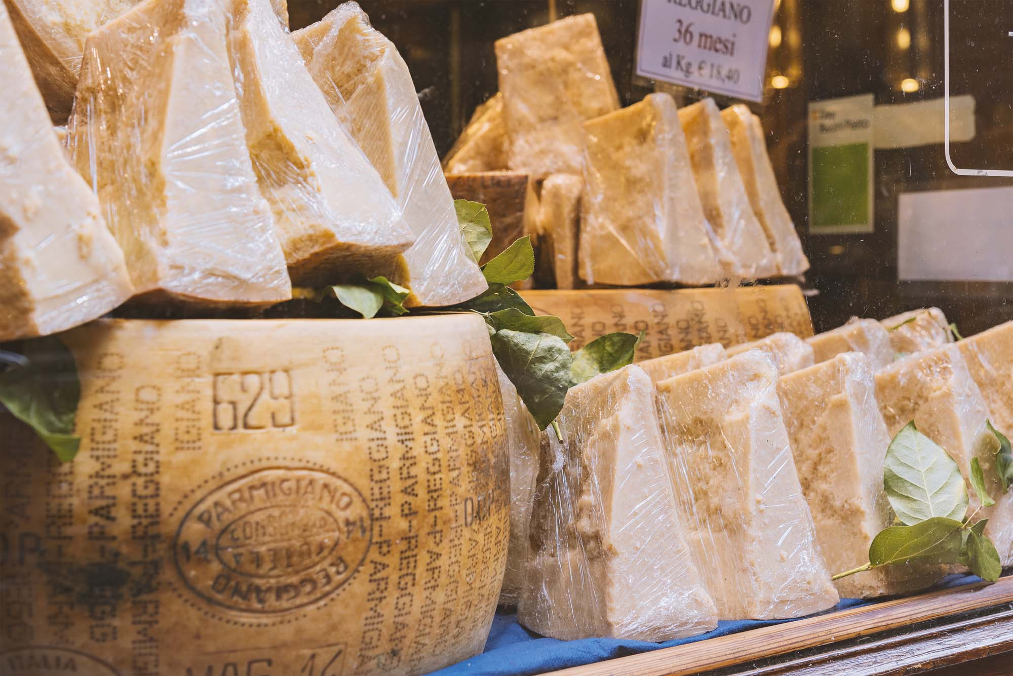 Cheese shop displaying Parmigiano-Reggiano cheeses.