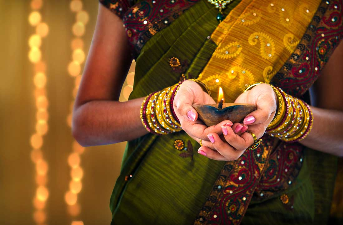 Girl holding candle at Diwali, Festival of Lights.