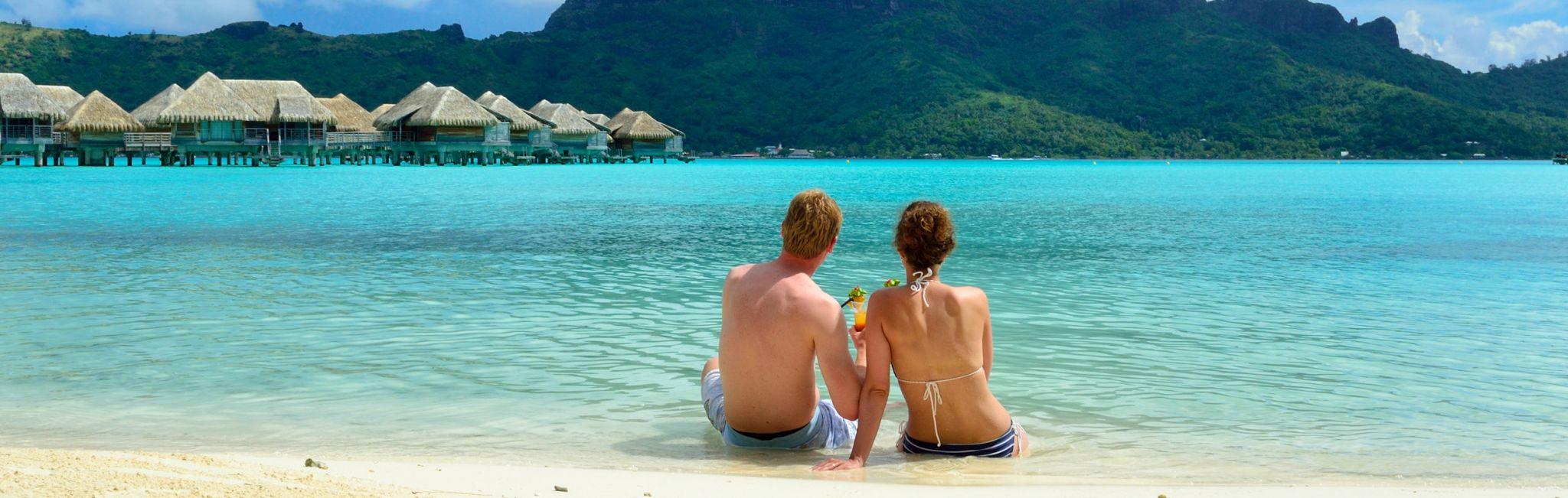 A couple relaxes on a beach in Bora Bora, Tahiti.