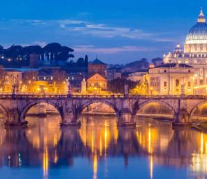 Skyline of St. Peter's Basilica at night reflecting off of the Tiber River
