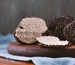 Black truffles mushrooms on rustic wooden table.