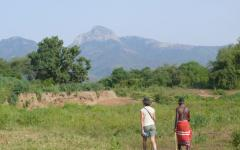 Tourist walking side-by-side with a Kenyan tribe member
