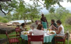 Group of tourists enjoying an authentic sit-down meal in the Kenyan wilderness with a Kenyan native