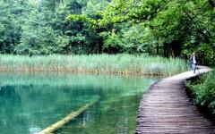 A person on a wooden walkway through Plitvice National Park in Croatia.