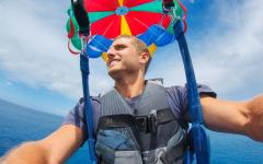 close up of man parasailing high in the sky