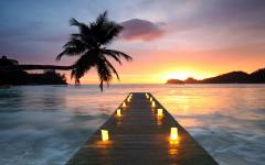 Romantic view of a Seychelles, Africa beach sunset with a pier lit with rows of candles