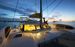 woman sitting on sailboat at sunset