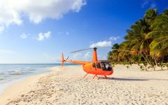 orange helicopter sitting on a deserted tropical beach