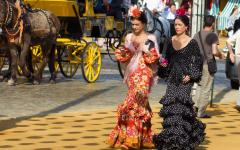Women wearing traditional dresses in Seville, Spain.