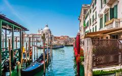 Beautiful view of traditional gondolas on Canal Grande in Venice, Italy with a cathedral in the background