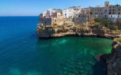 Polignano a Mare beach town on a cliff hanging over crystal clear seawater in Italy