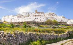 View of Ostuni, Italy on a hill surrounded by a rock wall