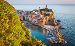 Coastal view of colorful buildings and boats in a Cinque Terre harbor in Liguria, Italy
