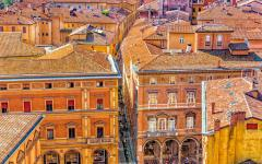 View from a rooftop looking down upon beige buildings in the town of Bologna, Italy