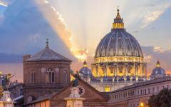 St. Peter's Basilica with sunlight peering through the clouds in the background in Vatican City, Italy