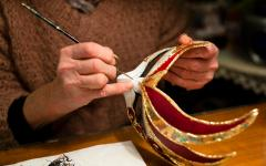 Woman painting and decorating a carnivale mask