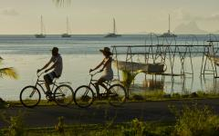 couple riding bikes at dusk along the seashore