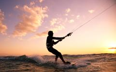 kite surfing on the ocean at sunset