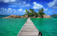 Pier leading to a secluded island on a Seychelles, Africa beach