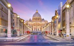 Street lit with street lights leading to St. Peter's Basilica at dawn
