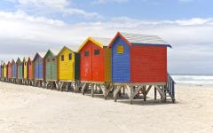 Row of colorful beach huts on a white sandy beach in South Africa