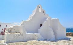 The white, battered walls of the Paraportiani Orthodox Church in Mykonos, Greece