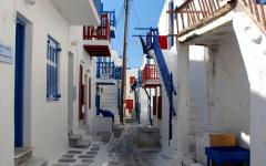 narrow stone street and white houses with blue doors and blue shutters