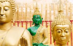 statue of an emerald buddha with two golden buddhas