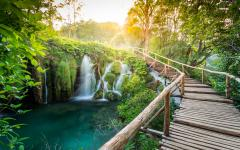 A wooden walkway runs close to some waterfalls in Plitvice National Park Croatia.
