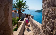 Tourists walk along the old walls in Dubrovnik, Croatia.