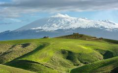 Snow covered Mount Etna with green rolling hills in the foreground in Sicily, Italy
