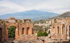 The beaten and battered ruins of the Teatro Greco ancient amphitheater in Taormina, Sicily, Italy