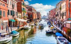A Venice, Italy canal filled with boats running through colorful buildings | Murano Island