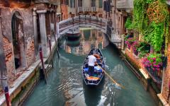 View of gondolier rowing his gondola through a Venice, Italy canal