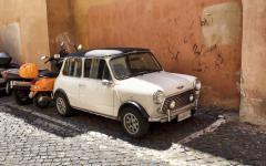 a Mini Cooper parked next to mopeds on a street in the trastevere neighbourhood, Rome.
