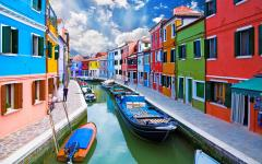 Boats parked on a canal running through colorful buildings on Burano Island, Venice, Italy