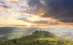 View of homes sitting on rolling green hills during sunset | Tuscany, Italy