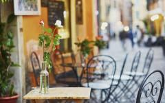 Flowers in a vase on a table with Roman streets in the background