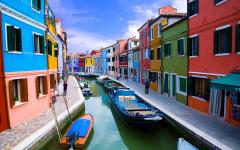 Boats parked on a canal running through colorful buildings on Burano Island, Italy