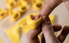 Tortelloni, typical Bolognese homemade fresh stuffed pasta in the preparation process at the moment of closing.