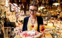 Woman holds up a traditional Italian appetizer in a local market, Bologna.