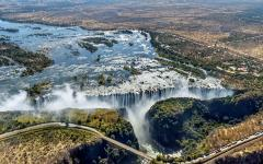 Aerial view of the Victoria Falls Bridge in the foreground of the beautiful Victoria Falls | Zimbabwe, Africa