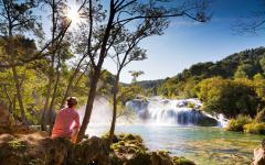 A woman admires a waterfall in Krka National Park, Croatia.