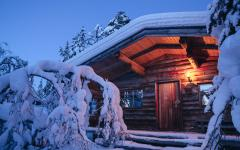 Snow covered cabin at dusk. Photo credit Kakslauttanen.