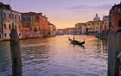 A lone gondola on the Grand Canal at sunrise, in Venice, Italy.