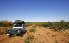 White safari jeep on a Botswana red dirt road