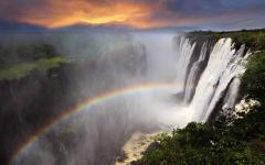 Gorgeous view of Victoria Falls at sunset with a rainbow forming in the mist | Zambia, Africa