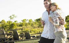 Loving couple embracing and enjoying white wine outside of their safari jeep | South Africa